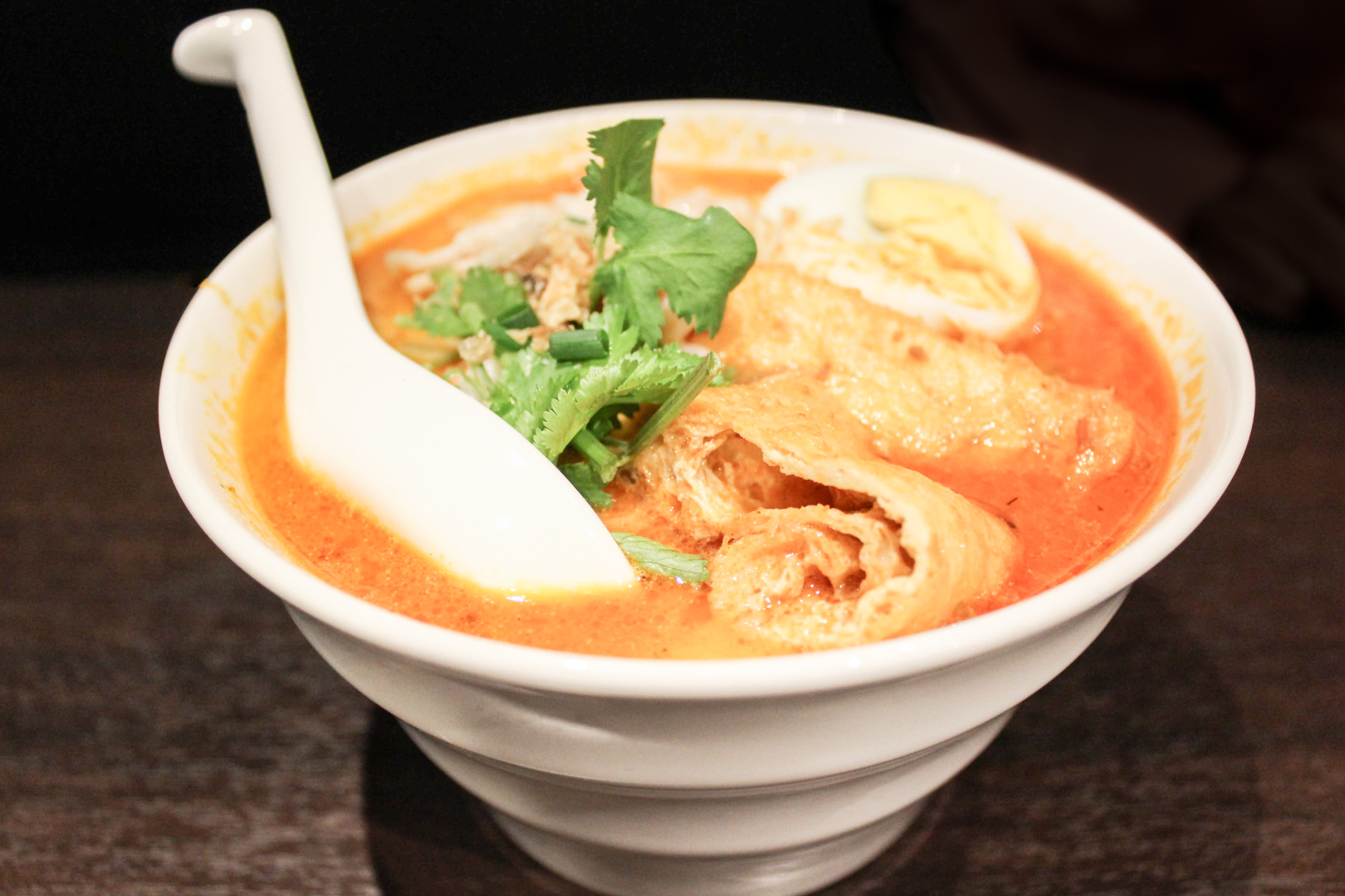 Halal restaurants in Tokyo - a bowl of spicy, orange-colored mi kari with a white spoon in it at Malay Asian Cuisine.