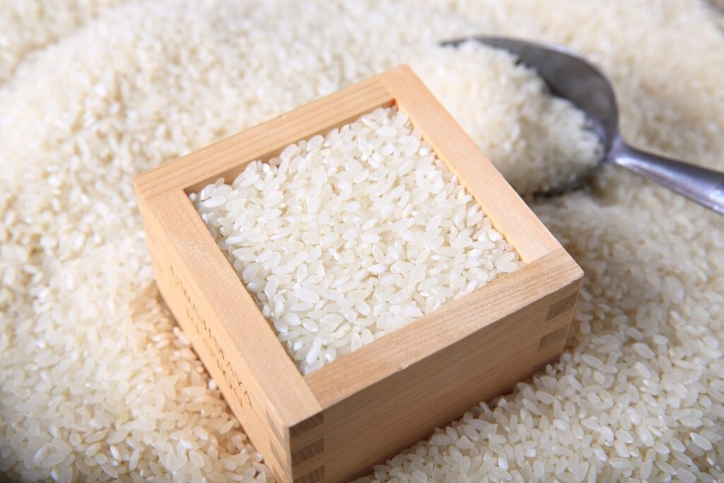 A square wooden masu cup is filled with rice and leveled off to show its usage as a measurement cup. It sits on a large open container of rice with a metal scoop to the right of the masu.