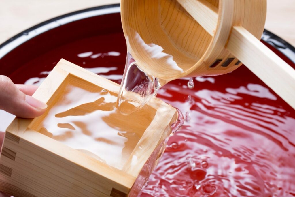 Drinking sake in a box: A wooden ladle is being used to abundantly pour sake from a barrel into a wooden masu cup.