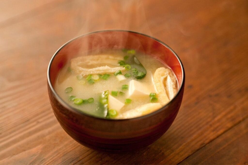 A steaming wooden bowl of miso soup with tofu and spring onions sits on a wooden table.