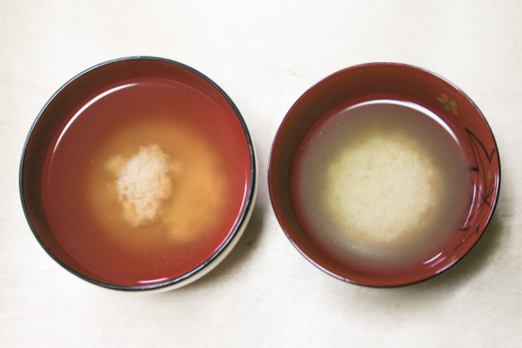 """Two bowls of miso soup side-by-side. The broth has separated from the miso paste and the miso has gathered in the middle of each bowl like a ball. The bowl to the right has a rounder """"ball,"""" while the one on the left has more miso at the base and a smaller amount at the top."""