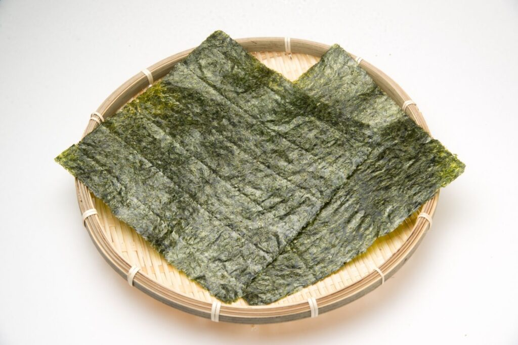 Two large sheets of dried nori Japanese seaweed sit in a shallow bamboo basket on a white surface.