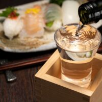 Sake in a box: A glass is set inside a wooden masu cup and is being filled to overflow. Behind it is a plate of sushi.