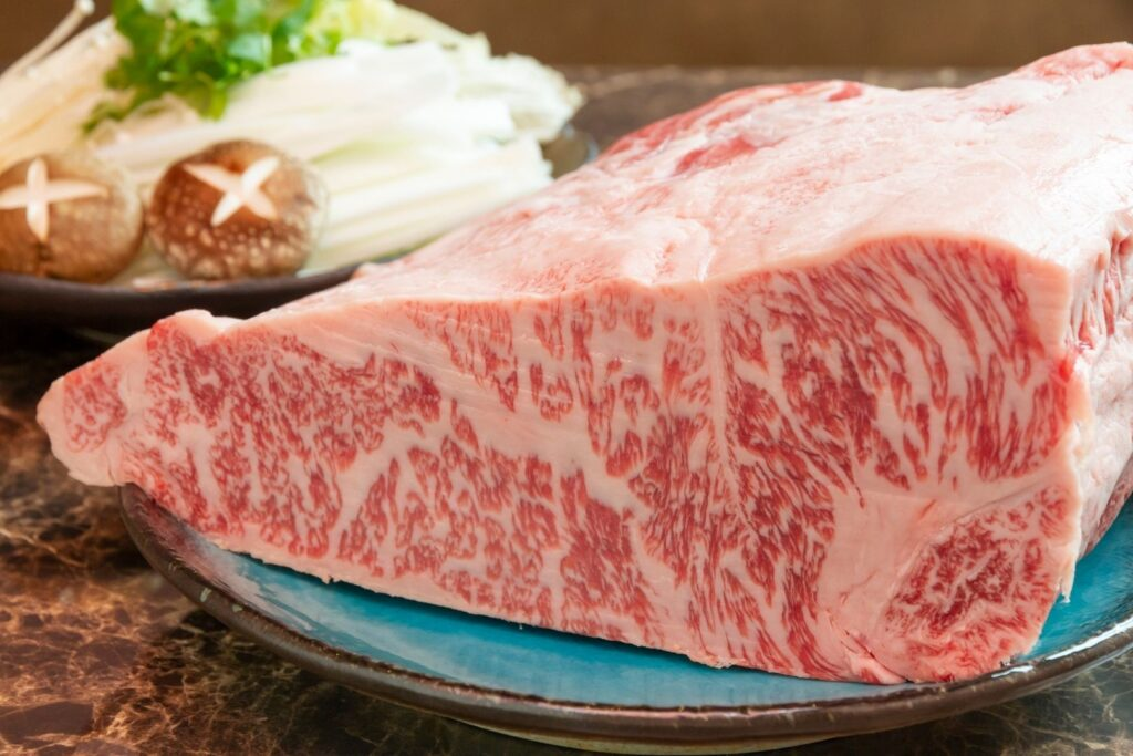 A large piece of beautifully-marbled wagyu sits on a blue plate ready to be cuts into slices. In the background, there is a plate of various vegetables waiting to be cooked. The Japanese system of wagyu grading is extremely strict, with the highest being a5 wagyu.