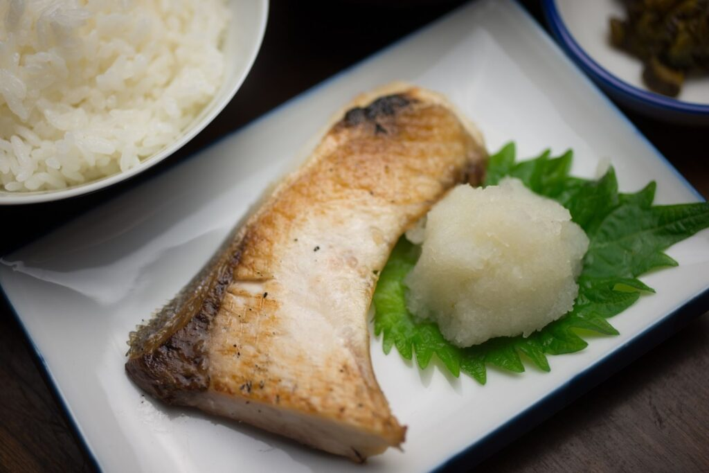 A piece of grilled buri served with grated radish and a shiso leaf. A bowl of white rice can also be partially seen in the top left-hand corner.