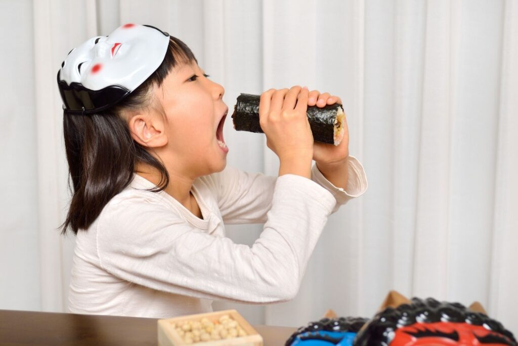 A young Japanese girl wears a mask on the top of her head while poised to eat her ehomaki facing the lucky direction of the year.
