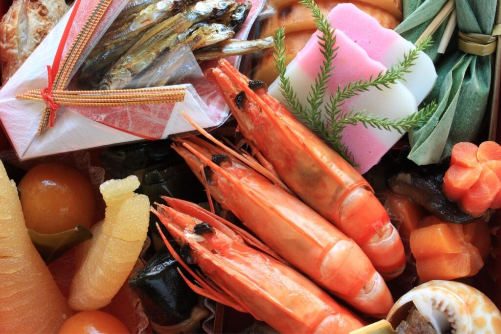An overheard shot of an osechi box with three shrimp as the focal point.