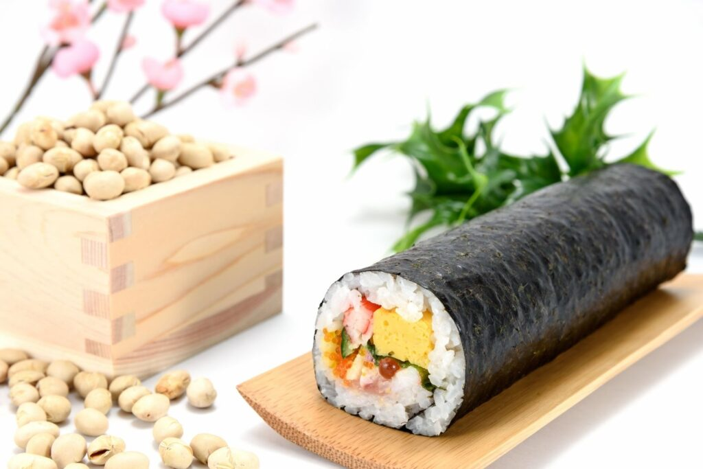 An ehomaki lucky direction sushi roll with seven fillings sits on a long wooden plate. To the left, is a wooden masu box overflowing with roasted soy beans, and in the background are some plastic cherry blossoms and sprigs of holly for decoration.
