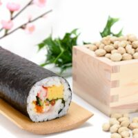 An ehomaki lucky direction sushi roll with seven fillings sits on a long wooden plate. To the right, is a wooden masu box overflowing with roasted soy beans, and in the background are some plastic cherry blossoms and sprigs of holly for decoration.