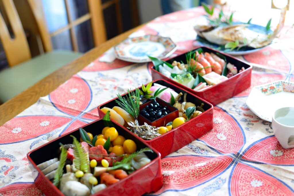 A three-tiered osechi ryori jubako box sits unstacked on a set table ready to be eaten. In the background is a whole fish on a separate plate.