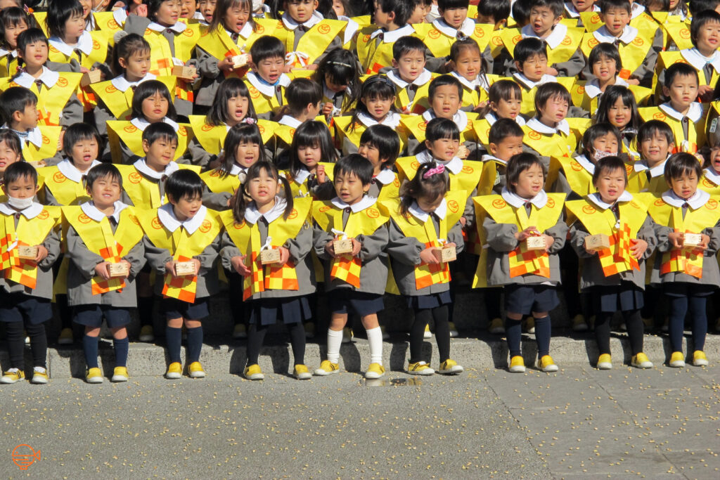 """Kindergarteners on the steps of Sensoji Temple, Tokyo. Roasted soy beans can be seen scattered all over the ground in front of them after having thrown them at the """"demon"""" during a mamemaki event."""