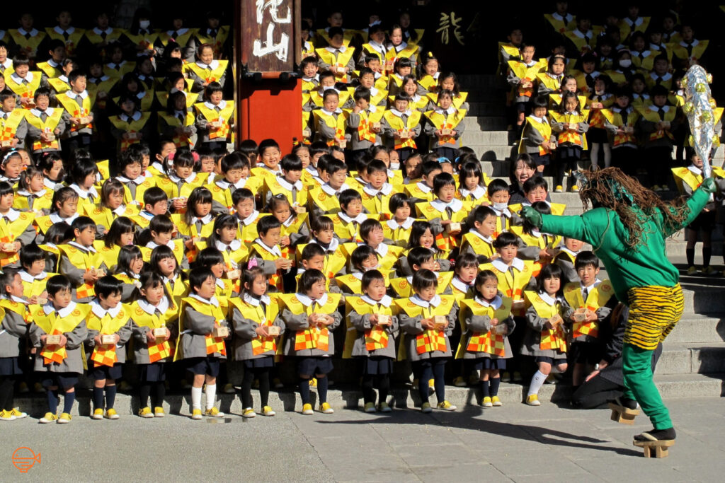 A person dressed as a demon wearing a long, brown wig, a full-body green suit with tiger print shorts over the top, and wearing elevated wooden shoes (gehta) while holding a mock club made of foil, approaches the group of kindergarten kids in their school uniforms on the steps of Sensoji Temple, Tokyo. The students are poised to throw their soy beans at the demon.
