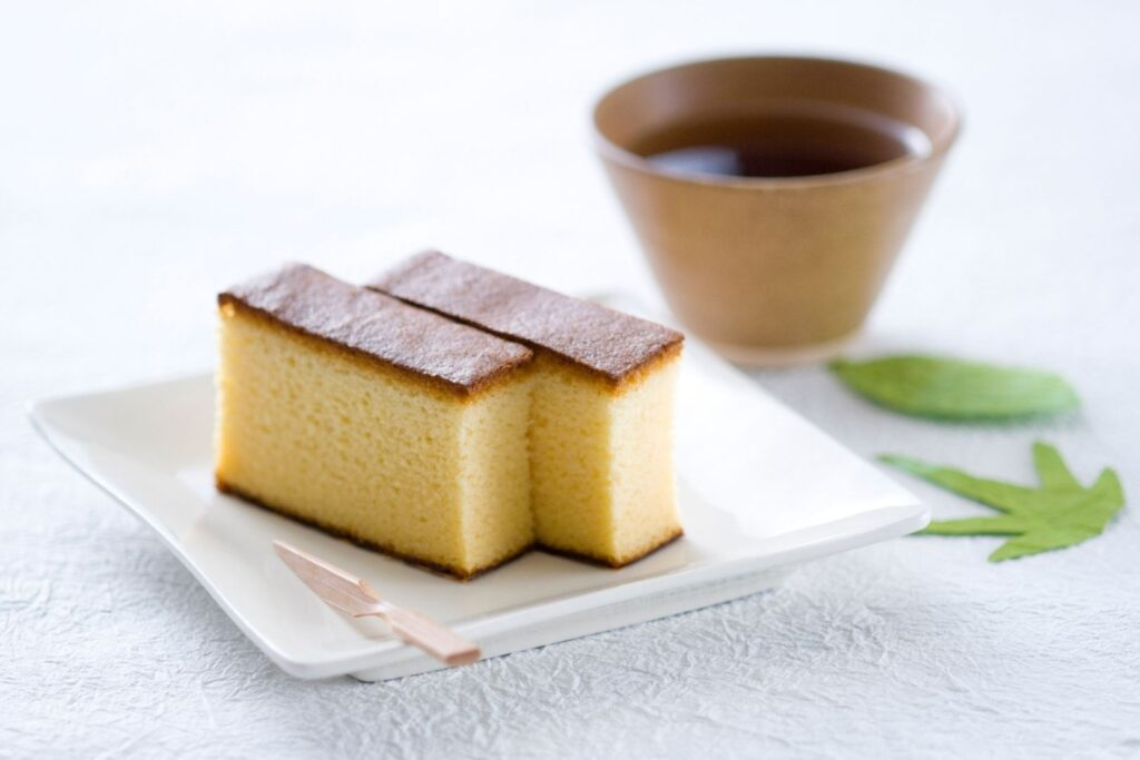 Nagasaki Food Guide: Two slices of castella, similar to a pound cake, on a plate with a cup of Japanese tea to the right and some green leaves on the table for decoration.