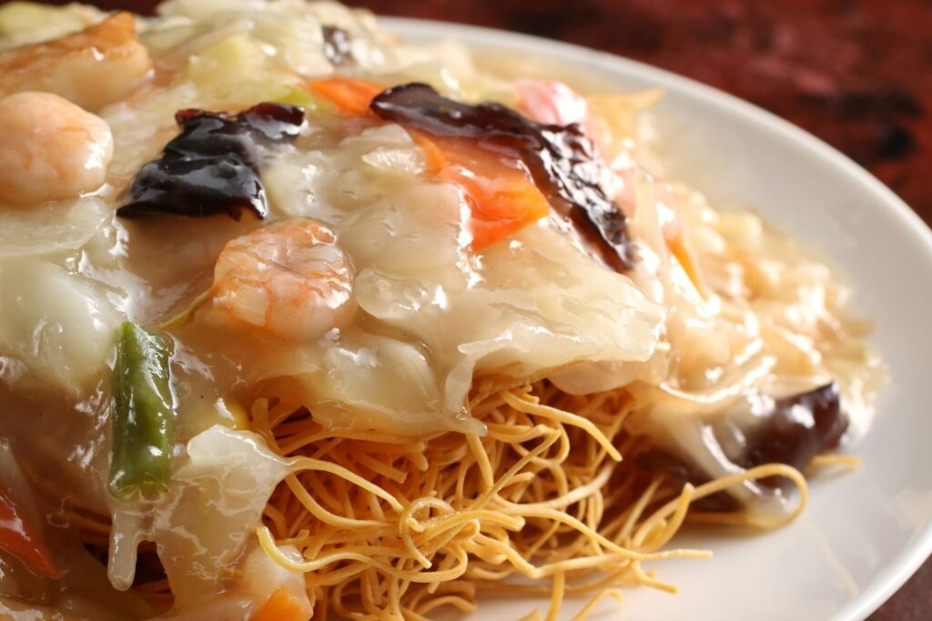 Nagasaki Food Guide: Crispy fried noodles topped with stirfried shrimp, cabbage, bean sprouts, and other vegetables.