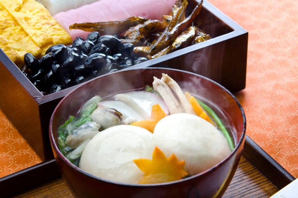 A hot bowl of ozoni soup sits in front of a box of osechi ryori. The soup contains large mochi rice cakes, oysters, decoratively-cut carrot and green vegetables.