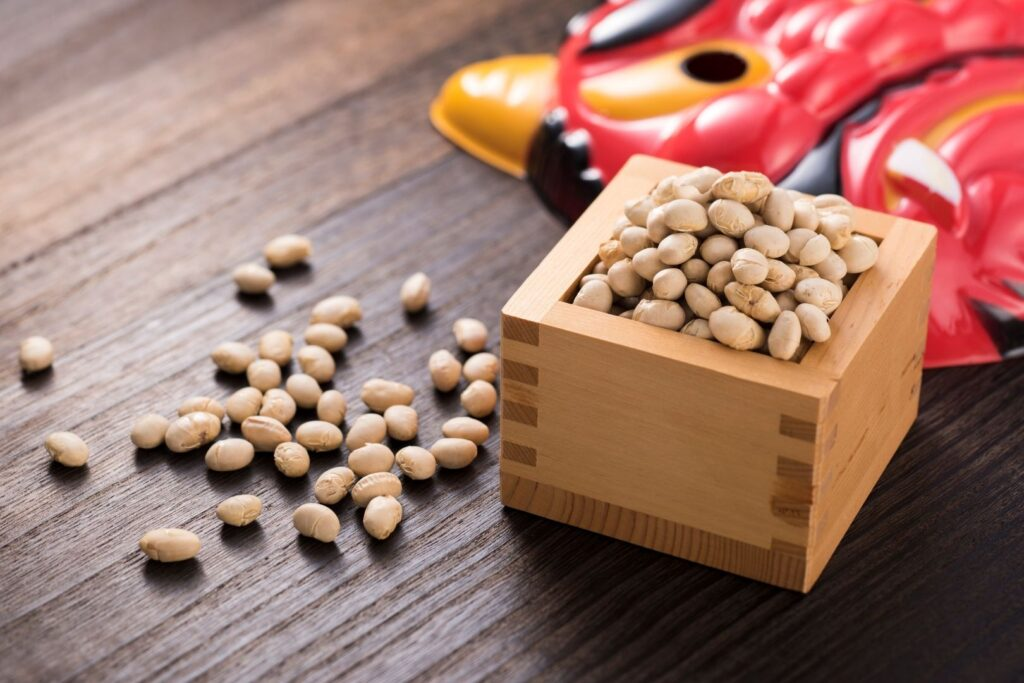 A wooden masu box filled with roasted soy beans, some scattered on the table to the left of the box. Behind the box is a red plastic demon mask.