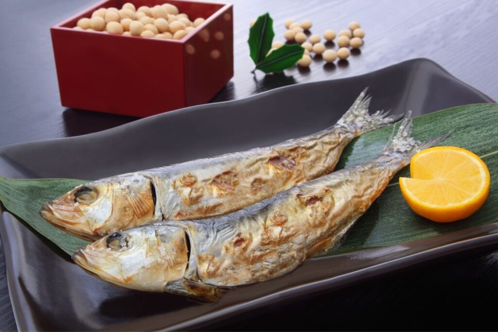 Two grilled sardines on a ceramic dish with some lemon. Behind that is a red wooden masu box filled with roasted soy beans. A sprig of holly sits to the right of the box along with some more soy beans scattered on the table.