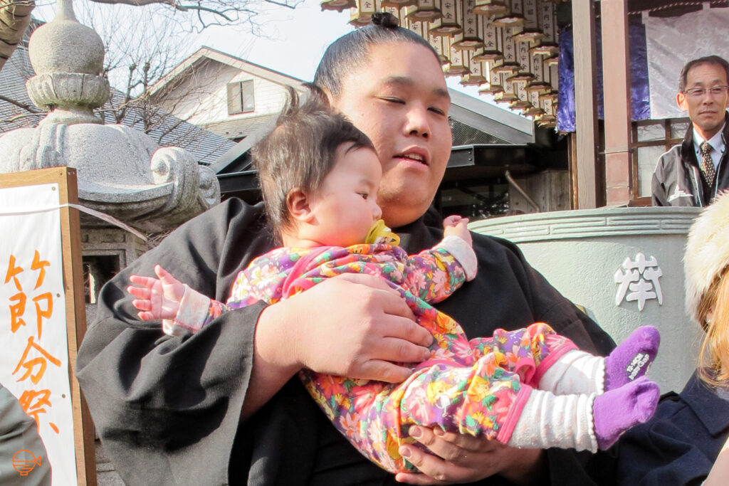 A sumo wrestler in a black robe and hair in a top-knot holds a baby with a yellow pacifier and wearing a pink multi-colored onsie after a mamemaki event at a shrine in Tokyo.
