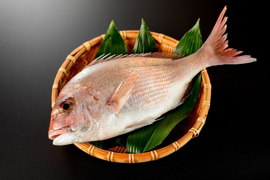 A red sea bream sits atop leaves in a shallow bamboo basket.