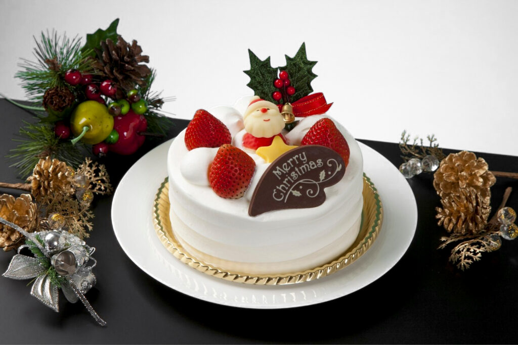 """A Christmas Cake decorated with holly and a bell, plus an edible Santa and star, and a chocolate plaque that says """"Merry Christmas"""". On the table around it are pine cones and other festive decorations."""