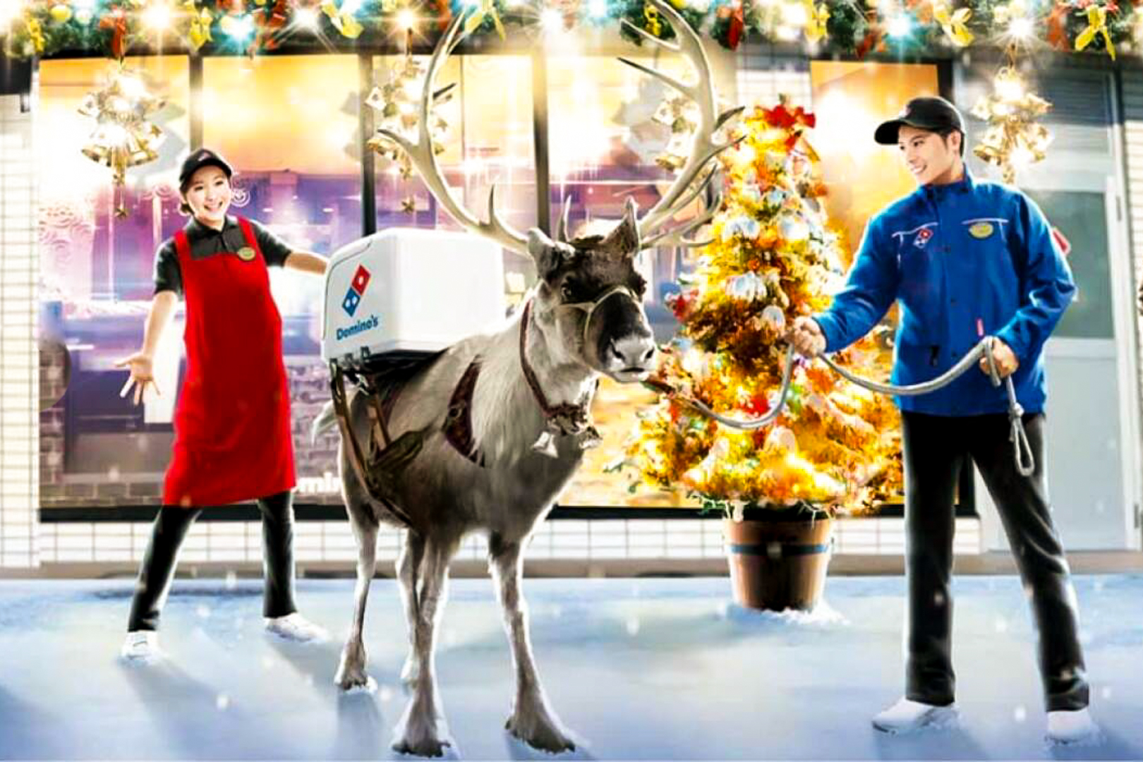 A reindeer with a Domino's delivery container strapped to its back stands outside a festively-decorated Domino's Japan store with a Christmas tree out front. Two staff members, a male staff member in blue holding the reindeer's reins and a female staff member in red with her hands outstretched, look on with delight.