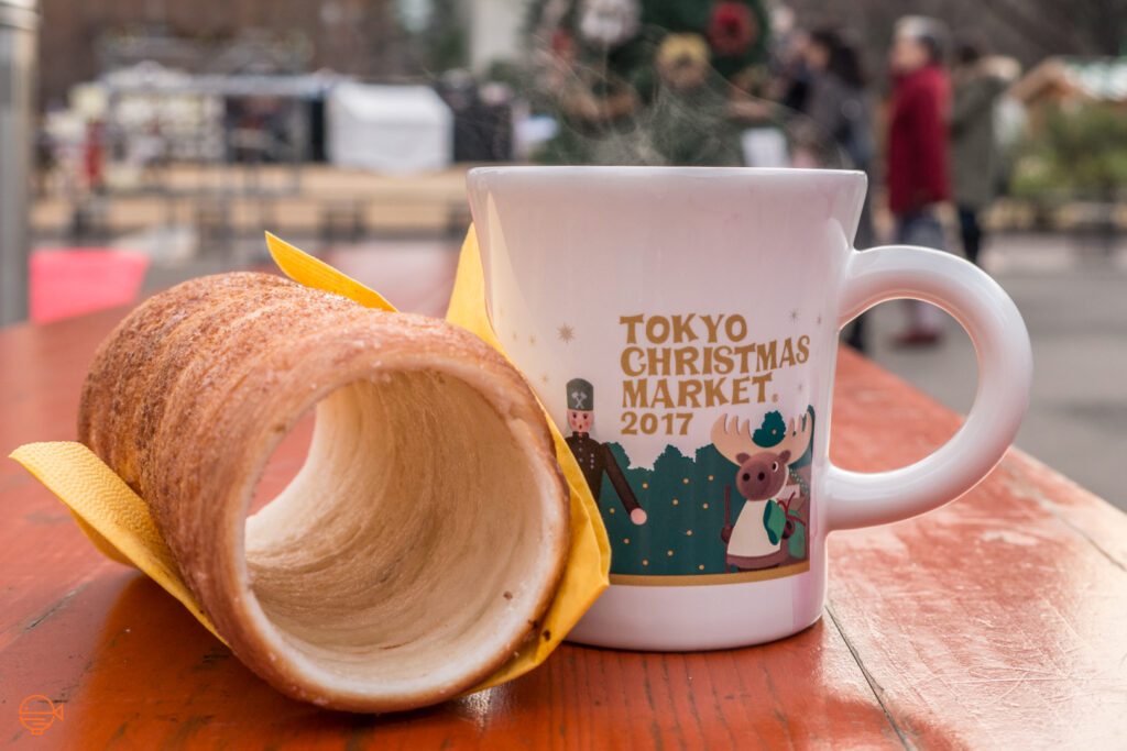 Christmas food in Japan: A cinnamon chimney cake next to a Tokyo Christmas Market mug for 2017 filled with hot mulled wine sits on a wooden table.